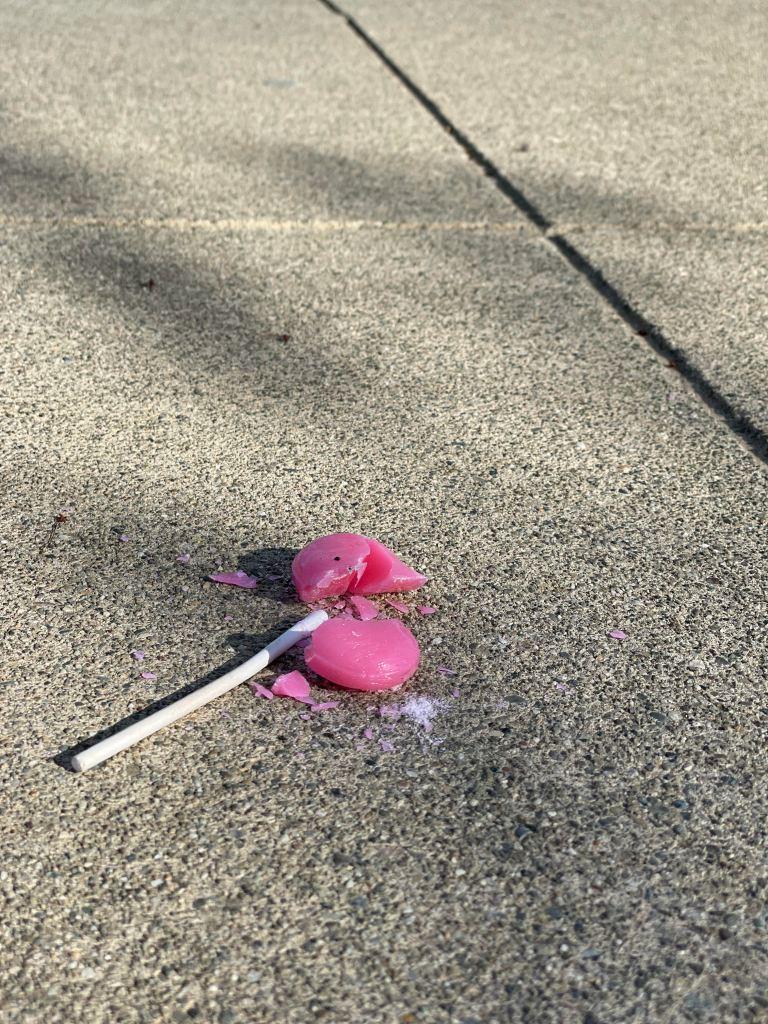 Broken lollipop on sidewalk