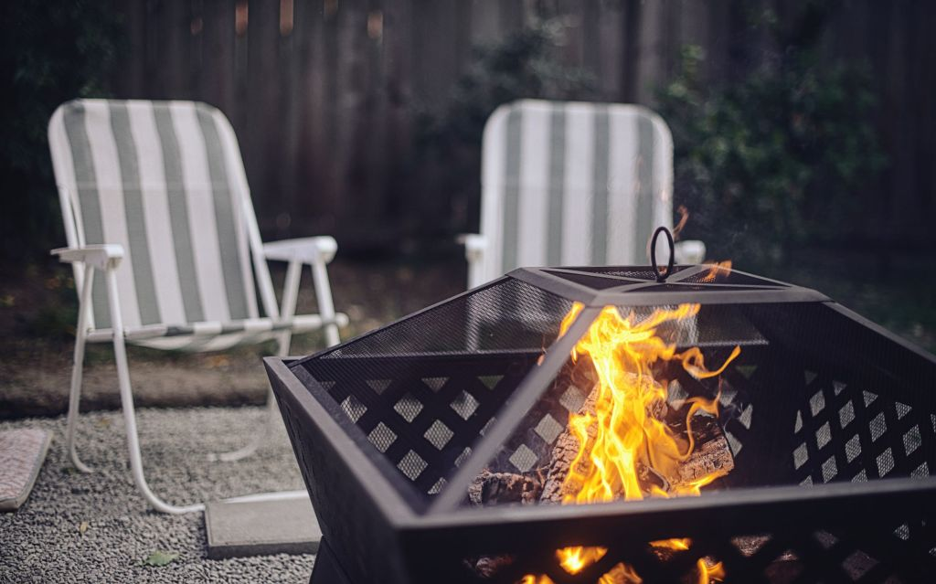 Two folding chairs by a fire